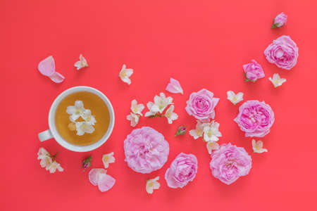 Cup of tea with white jasmine and pink roses flower bouquet on pink red background Stock Photo