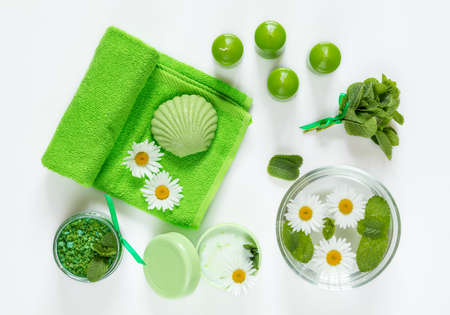 Spa products. Mint bath salts, fresh herbs, soap, cosmetic cream, candles and towel. Green color concept. Flat lay on white background, top view. Stock Photo
