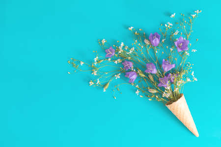 Three waffle cones with blue bells and white flowers blossom bouquets on blue surface. Flat lay, top view floral background. Stock Photo