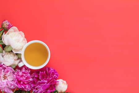 Cup of tea with white and pink peonies flower bouquet on pink red background Stock Photo - 102826678