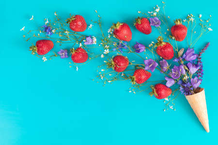 Waffle cone with wild strawberry and blue bells and white flowers blossom bouquets on blue surface. Flat lay, top view sweet food floral background. Stock Photo - 102826679
