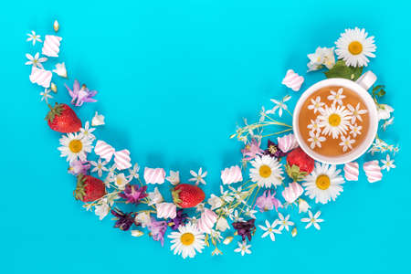 Cup of tea with fresh strawberries, marshmallows and flowers blossom bouquets on blue surface. Flat lay, top view sweet food floral background. Stock Photo