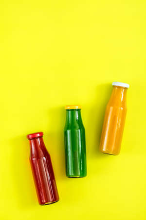 Beautiful food art background. Yellow, red and green juices in glass bottles on bright green surface. Stock Photo