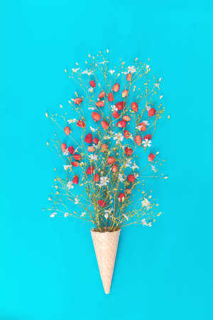 Waffle cone with wild strawberry and white flowers blossom bouquets on blue surface. Flat lay, top view sweet food floral background.