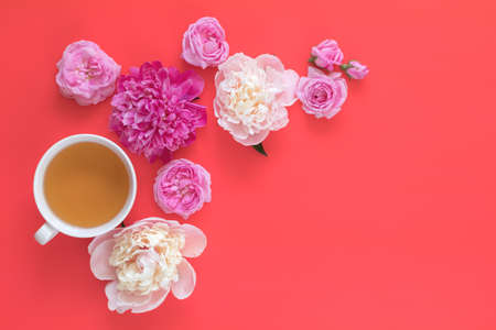 Cup of tea with white and pink peonies and pink roses flower bouquet on pink red background