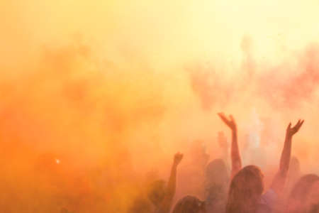 People dancing during Colorful Holi Festival. Blurred sunny sunset multicolor background. Stock Photo
