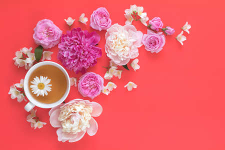 Cup of tea with white and pink peonies, jasmine, daisy and pink roses flower bouquet on pink red background
