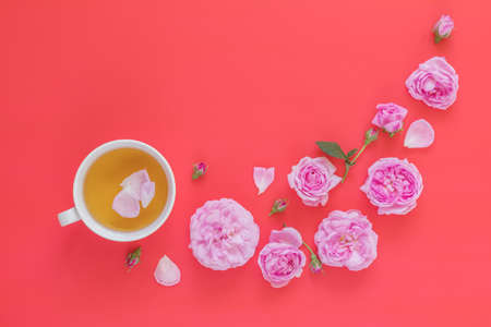 Cup of tea with pink roses flower bouquet on pink red background Stock Photo - 102826723