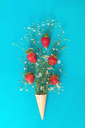 Waffle cone with strawberry and white flowers blossom bouquets on blue surface. Flat lay, top view sweet food floral background. Stock Photo