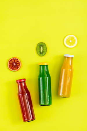 Beautiful food art background. Yellow, red and green juices in glass bottles sliced lemon, kiwi and blood orange fruit on bright green surface. Stock Photo