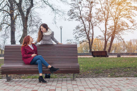 Two happy cute beautiful female teenagers at the bench in an autumn city park Stock Photo