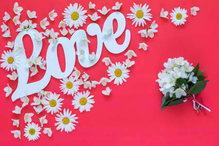 White letters forming word LOVE written with chamomile flowers and jasmine bouquet on pink background. St. Valentines Day, wedding holiday concept. Stock Photo