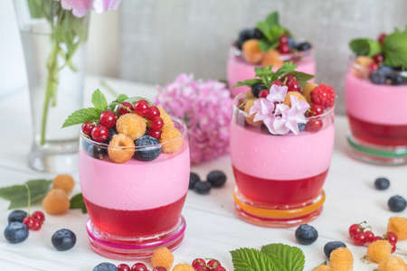 Multivitamin summer berry delicious panacotta. Sweet food with raspberries, blueberries, currants, croutons and mint, pink hydrangea bouquet, light background.
