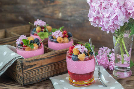 Multivitamin summer berry delicious panacotta. Sweet food with raspberries, blueberries, currants, croutons and mint, pink hydrangea bouquet, dark wooden background.
