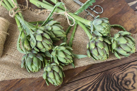 Two artichoke bouquets on kitchen table among some kitchen items Stock Photo