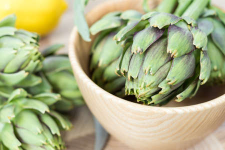 Artichoke bouquets in wooden bowl and lemon on kitchen table, close up. Stock Photo