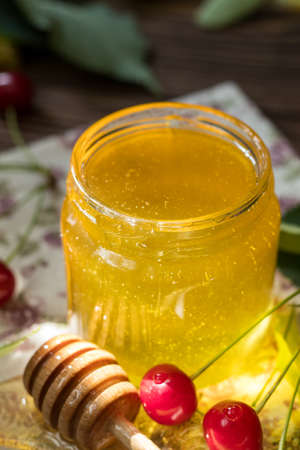 Open glass jar of liquid honey and honey dipper, bunch of linden flowers and red cherry on wooden surface. Ray of sunlight. Dark rustic style.