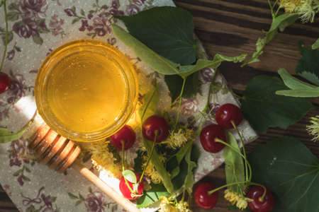 Open glass jar of liquid honey and honey dipper, bunch of linden flowers and red cherry on wooden surface. Ray of sunlight. Dark rustic style. Top view, copy space.