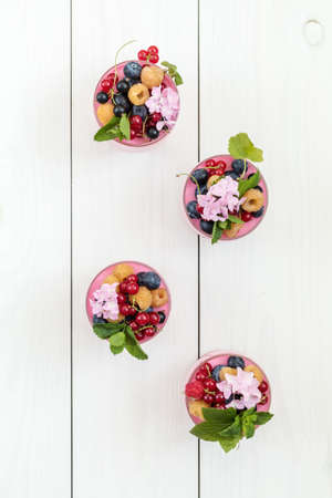 Multivitamin summer berry delicious panacotta. Sweet food with raspberries, blueberries, currants, croutons and mint, pink hydrangea bouquet, white wooden background, top view, copy space.