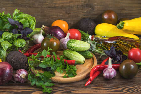 Many delicious fresh juicy colorful summer vegetables and herbs on dark wooden background. Close up, shullow depth of the field. Healthy eating concept background. Stock Photo