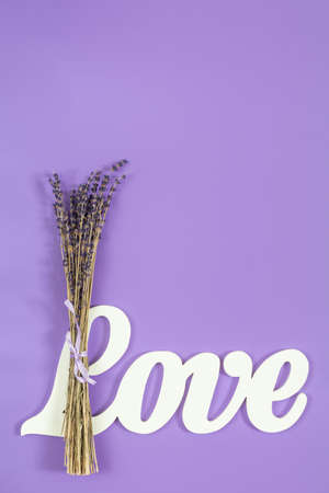 White letters forming word LOVE written with beautiful dried lavender bouquet on violet surface. Top view, copy space. St. Valentines Day, wedding holiday concept.