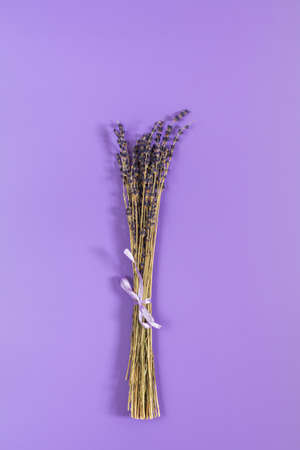 Beautiful dried lavender bouquet on violet surface. Top view, copy space. Nice holiday wedding valentin birthday card. Stock Photo