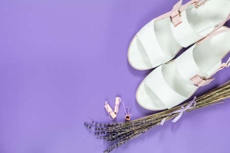 Fashionable sandals and Beautiful dried lavender bouquet on violet surface. Top view, copy space. Nice holiday wedding valentin birthday card.