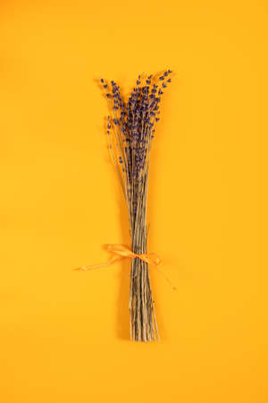 Beautiful dried lavender bouquet on yellow surface. Top view, copy space. Nice holiday wedding valentin birthday card. Stock Photo