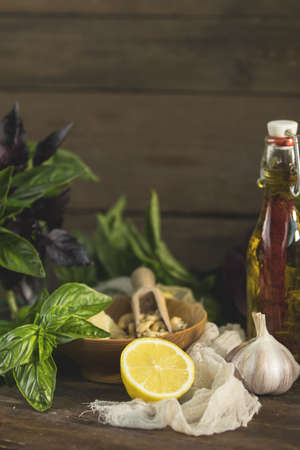 Many food ingredients for making pesto on dark wooden background. Green basil, cedar nuts, cashews, lemon, garlic, olive oil, parmesan cheese. Shallow depth of the field, toned and processing photo.