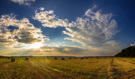 Dramatic sunset over a fields. Straw bales in fields farmland with blue cloudy sky at harvesting time. Field in the amazing beautiful colorful summer sunset. Beautiful thunder clouds over the field. Stock Photo