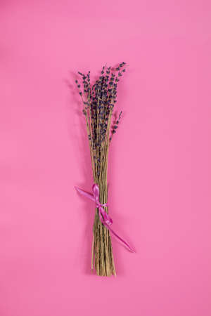 Beautiful dried lavender bouquet on pink surface. Top view, copy space. Nice holiday wedding valentin birthday card.