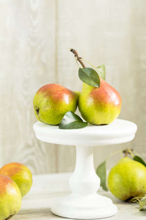 Many juicy beautiful amazing nice pears on light wooden background. Beautiful food art background.