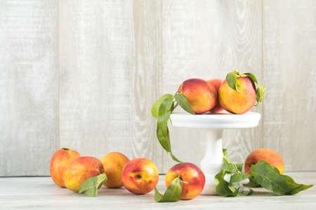 Many juicy beautiful amazing nice peaches on light wooden background. Beautiful food art background.