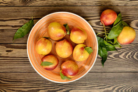 Many juicy beautiful amazing nice peaches on dark wooden background. Beautiful food art background. Top view, copy space. Stock Photo