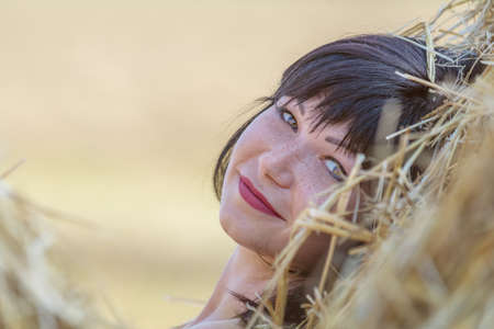 Portrait cute happy beautiful female brunette with red lipstick against a background of wheat field at the time of the sunset. Shallow depth of the field, toned and processing photo.