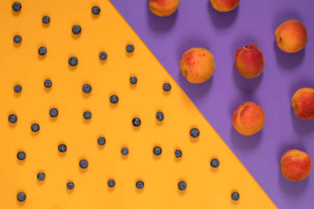 Many juicy beautiful amazing nice peaches and blueberries on violet and yellow surface. Beautiful food art background. Top view, copy space.