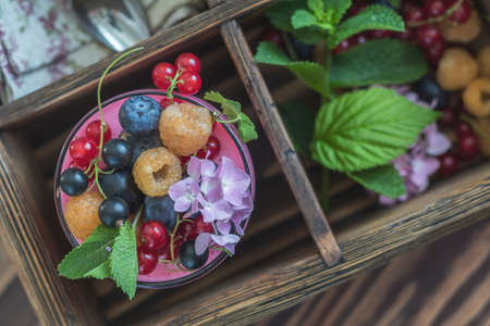 Multivitamin summer berry delicious panacotta. Sweet food with raspberries, blueberries, currants, croutons and mint, pink hydrangea bouquet, dark wooden background, top view.