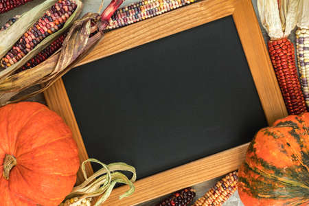 Holiday Halloween background with indian multicolored corn, pumpkin and slate blackboard, top view.