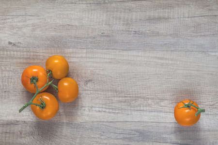 Branch yellow tomatoes on light wooden surface. Top view, copy space. Stock Photo