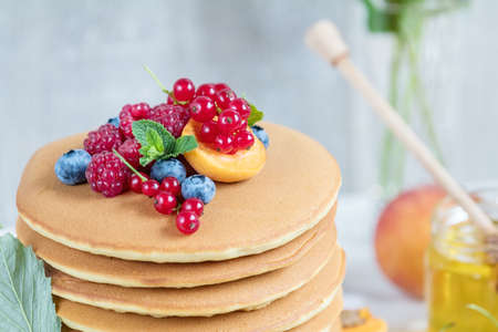Fresh delicious pancakes with summer raspberries, blueberries, red currants, apricot, peach and mint. Pink phlox bouquet, two glasses of orange juice, honey, light background. Sweet nutritious food.