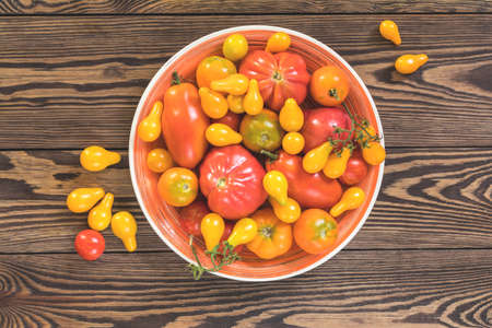 Many different red orange yellow tomatoes on dark wooden surface.  Beautiful food art background, top view. Stock Photo - 107033850