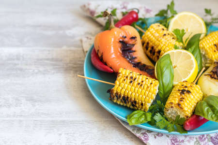 Corn baked in olive oil, with pepper, salt and basil on blue dish on a light surface. Vegetarian, vegan menu Stock Photo - 107033852