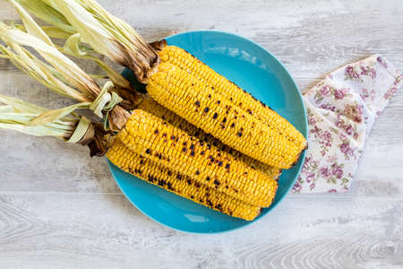 Corn baked in olive oil and salt on blue dish on light surface. Vegetarian, vegan menu Stock Photo