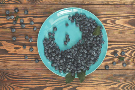Many juicy beautiful amazing nice blueberries in blue dish on dark wooden background. Beautiful food art background. Top view, copy space. Stock Photo