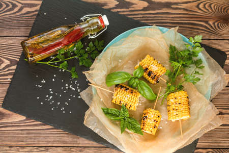 Corn baked in olive oil, with pepper, salt and basil on blue dish on a black stone on dark wooden surface. Vegetarian, vegan menu