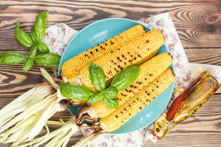 Corn baked in olive oil and salt on blue dish on dark surface. Tasty grilled corn cobs on old table in the open air.