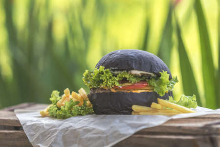 Burger made with black charcoal bun served with potato wedges, lettuce and sauce on wooden rustic table Close up, shallow depth of the field. Stock Photo