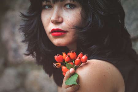 Red rose hips in womens hands. Sexy beautiful pretty brunette with red lipstick. Selective focus, shallow depth of the field. Face out of focus. Stock Photo