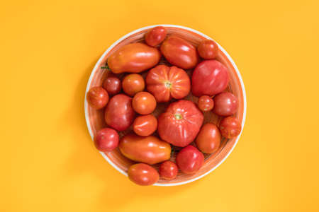 Many different red  tomatoes on yellow surface. Beautiful food art background, top view.