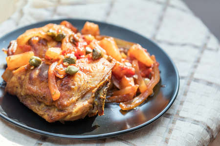 Delicious baked chicken with vegetables and capers in black dish on the table.